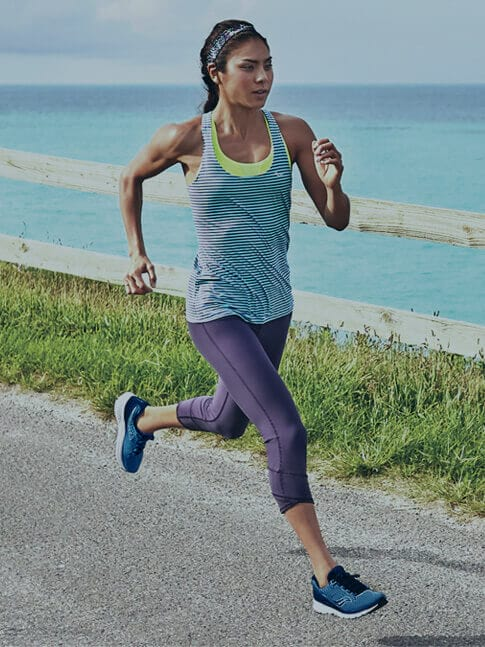 Woman running by the ocean and wearing Women's Saucony Liteform Escape